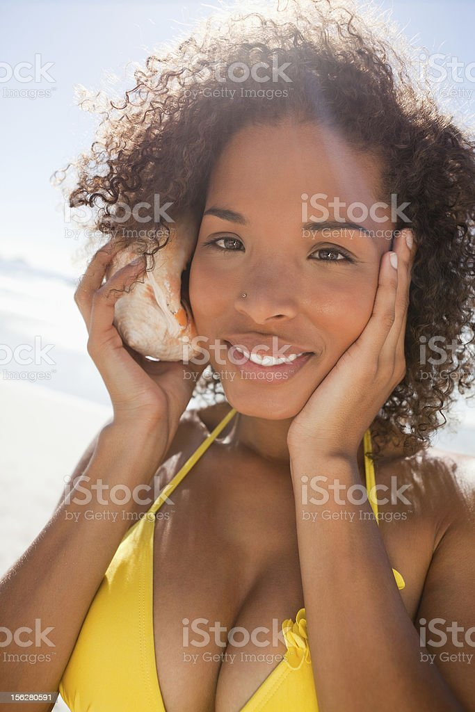 Woman listening through a seashell while placing her hand on royalty-free stock photo