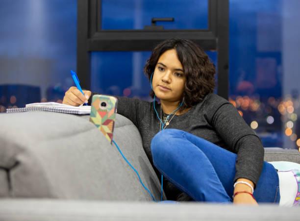 mujer escuchando una clase a través de su teléfono celular - gerardo huitrón fotografías e imágenes de stock