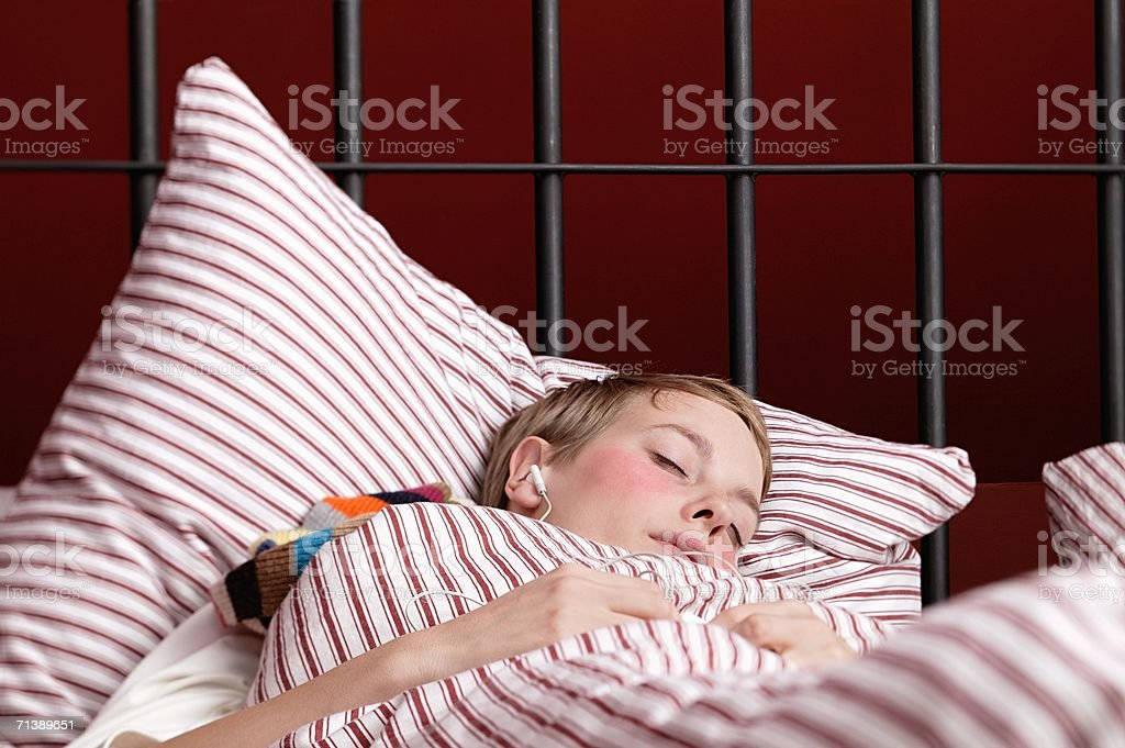 Woman listening to an mp3 player in bed royalty-free stock photo