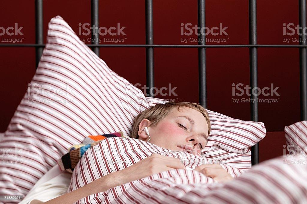 Mujer escuchando su reproductor de mp3 en la cama foto de stock libre de derechos