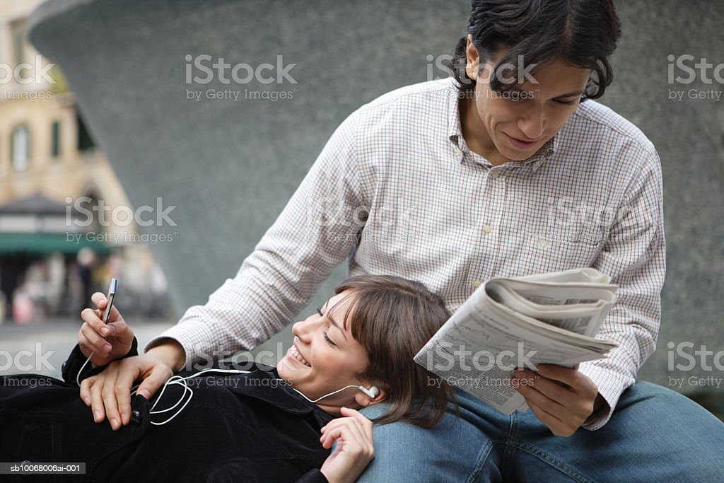 Woman listening to headphones lying head on man reading newspaper outdoors foto royalty-free