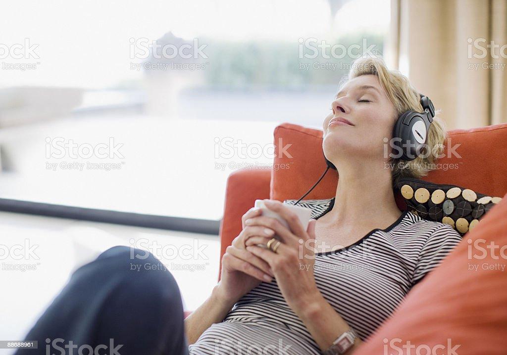 Woman listening to headphones on sofa stock photo