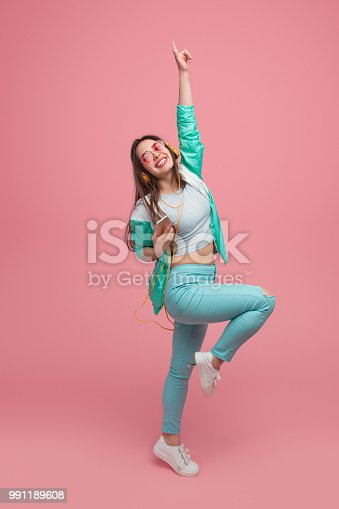istock Woman listening to music and dancing in studio 991189608