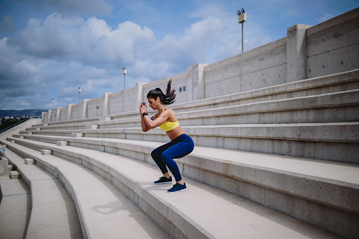 Woman listening to music and exercising on urban stairs