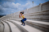 Athletic woman with smartwatch listening to music and doing jump squats on urban stadium stands