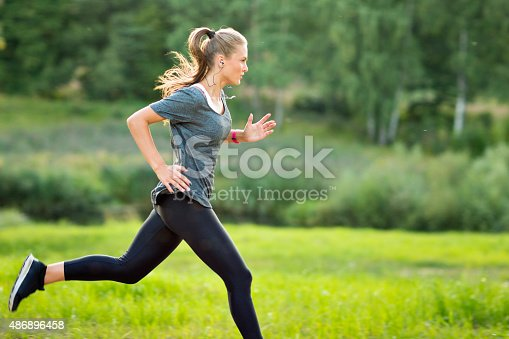 istock Woman listening to music and running in park 486896458