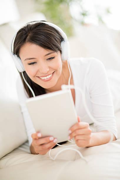 mujer escuchando música en su hogar - mp4 fotografías e imágenes de stock