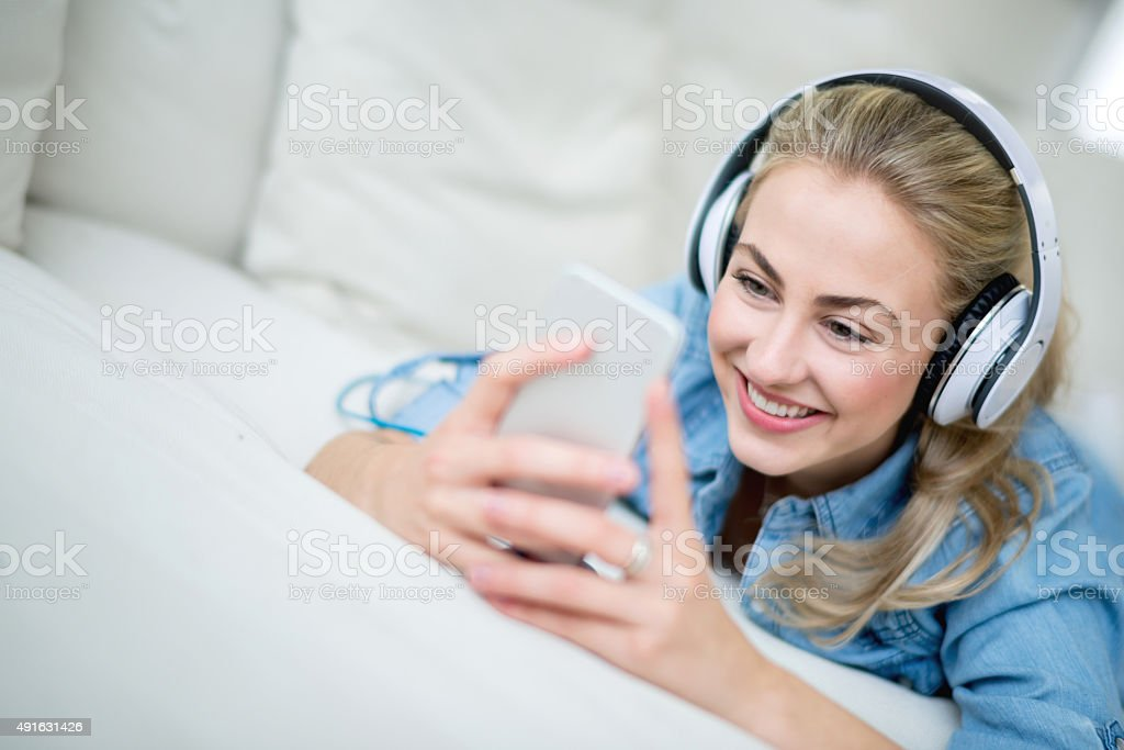 Woman listening to music at home stock photo