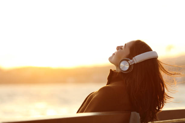 Woman listening to music breathing on a bench in winter stock photo