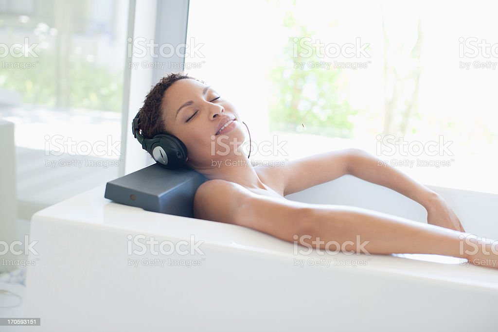 Woman listening to music in bathtub royalty-free stock photo