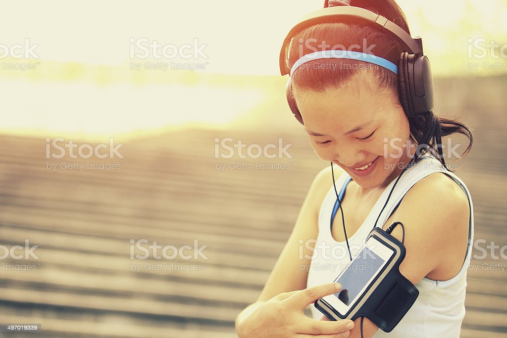 woman listening to music in headphones  from smart phone mp3 stock photo