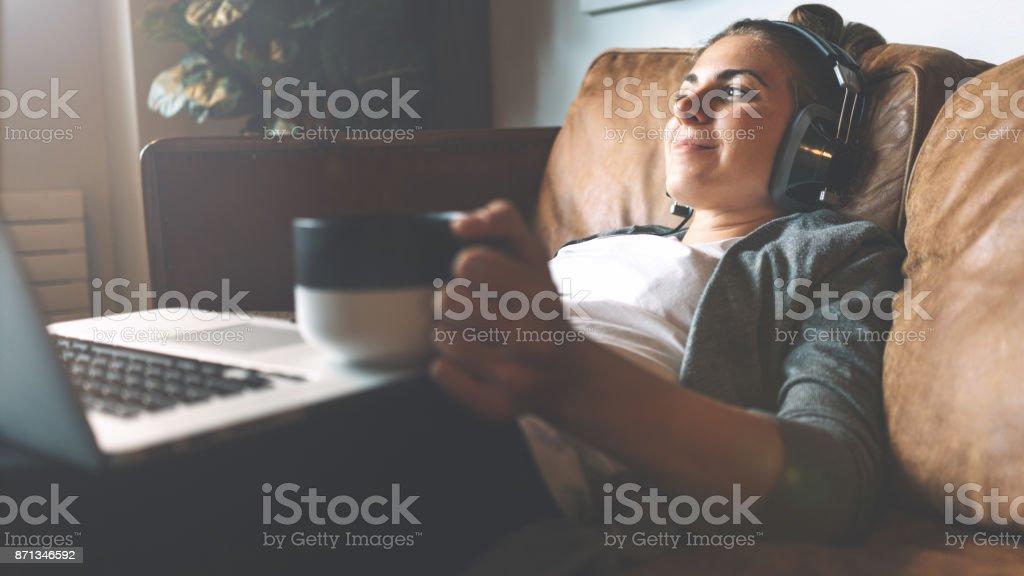 Frau anhören von Musik im Kopfhörer auf gemütlichen sofa – Foto