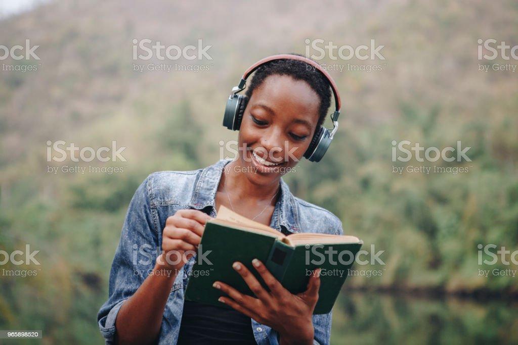 Vrouw luisteren naar muziek in de natuur - Royalty-free Boek Stockfoto
