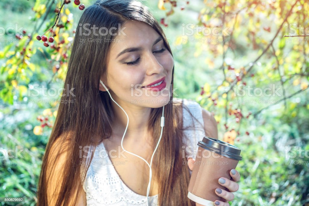 Woman listening to music in your phone wearing headphones on a Sunny day. Concept of audiobooks and student education stock photo