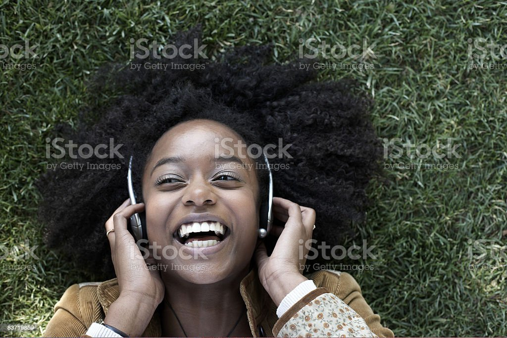 Woman listening to music lying on grass royalty-free stock photo