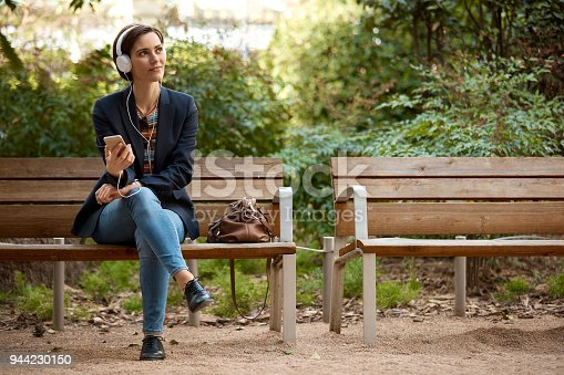 Full length of woman listening music with headphones and mobile phone. Thoughtful female is sitting on wooden bench in park. She is relaxing while looking away outdoors.