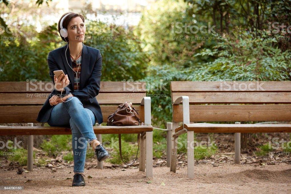 Frau anhören von Musik auf Bank im park – Foto