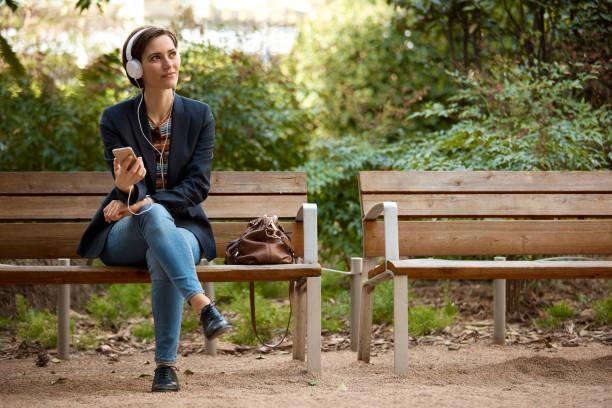 kvinna lyssna på musik på bänken i parken - bench bildbanksfoton och bilder