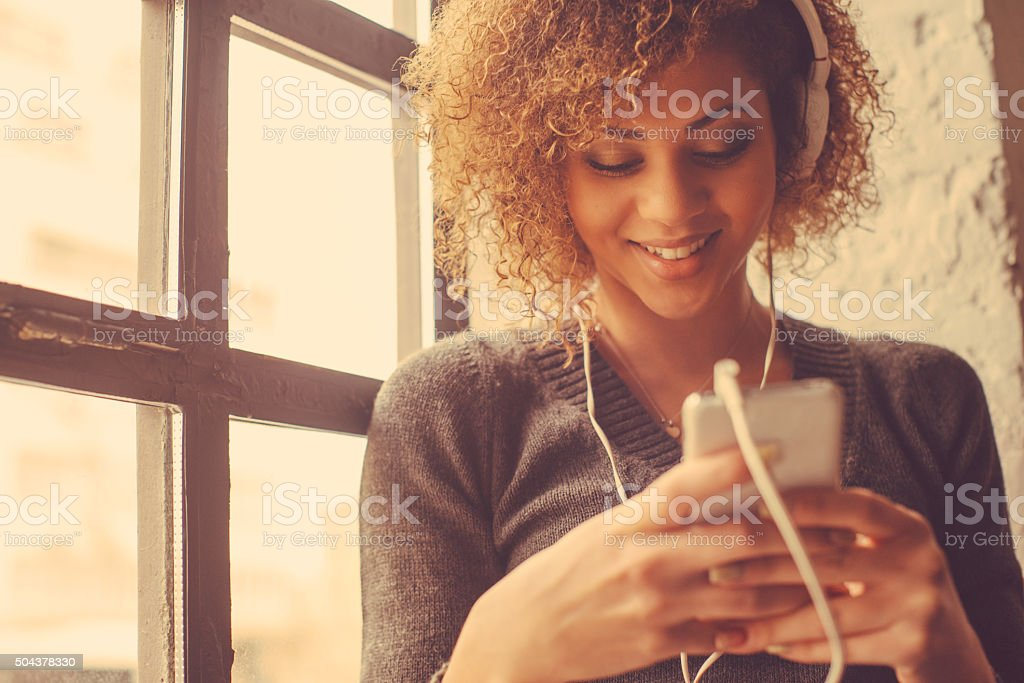 Portrait of young beautiful woman using smart phone and listening to...