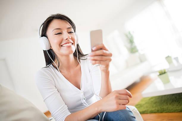 mujer escuchando música en su teléfono - mp4 fotografías e imágenes de stock