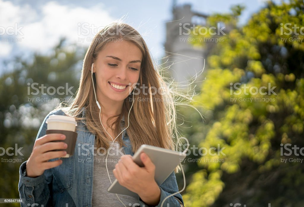 Woman listening to music on her tablet outdoors stock photo