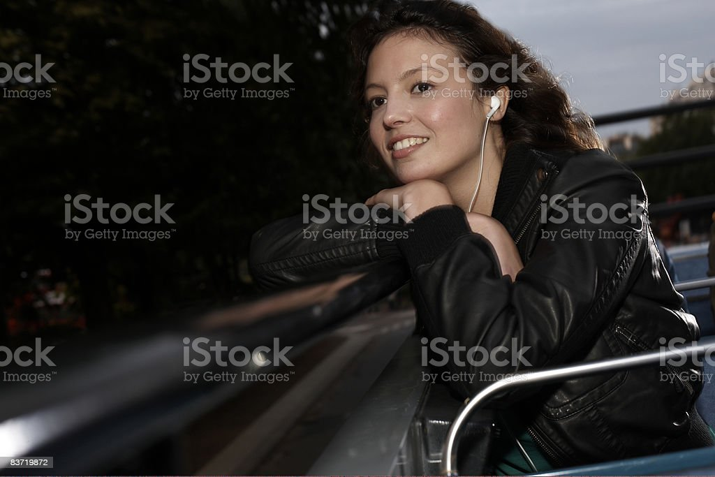 Woman listening to music on open top bus royalty-free stock photo
