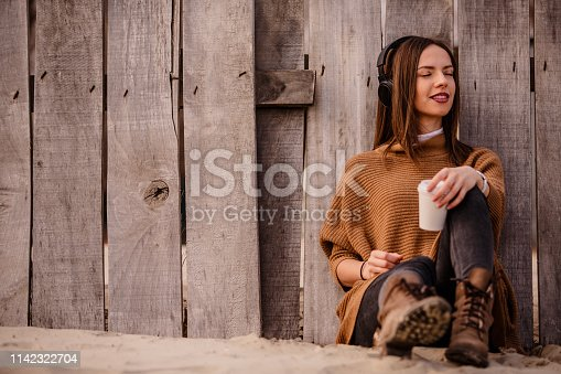 Young woman drinking coffee on the beach and listening to music.