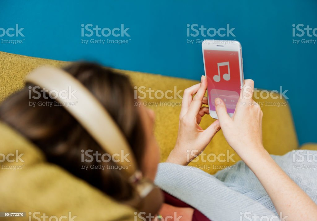 Woman listening to music on the sofa royalty-free stock photo