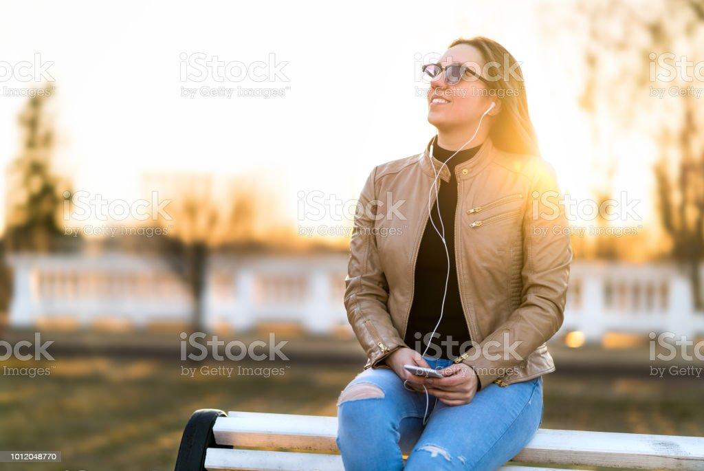 Mulher ouvindo ao ar livre de música. Feliz sorridente senhora sentada no banco do Parque segurando o telefone móvel no pôr do sol. Ouvir o audiobook. - foto de acervo