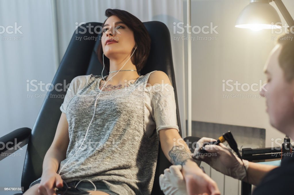 Woman listening to music while doing tattoo royalty-free stock photo