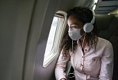 Portrait of an African American woman listening to music while flying on an airplane wearing a facemask during the COVID-19 pandemic