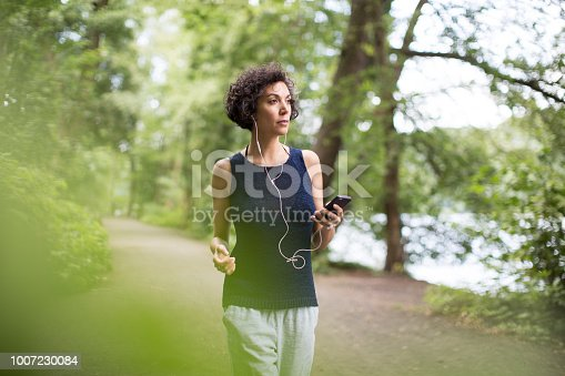 Woman listening to music on in-ear headphones using mobile phone. Confident mature female is walking on road. She is wearing casuals in forest.