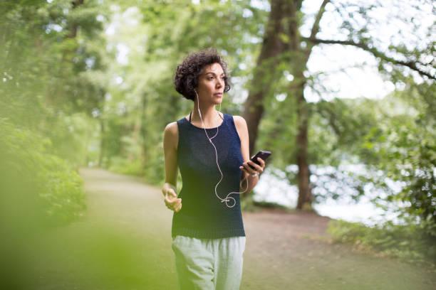 Anhören von Musik bei einem Spaziergang im Wald Frau – Foto