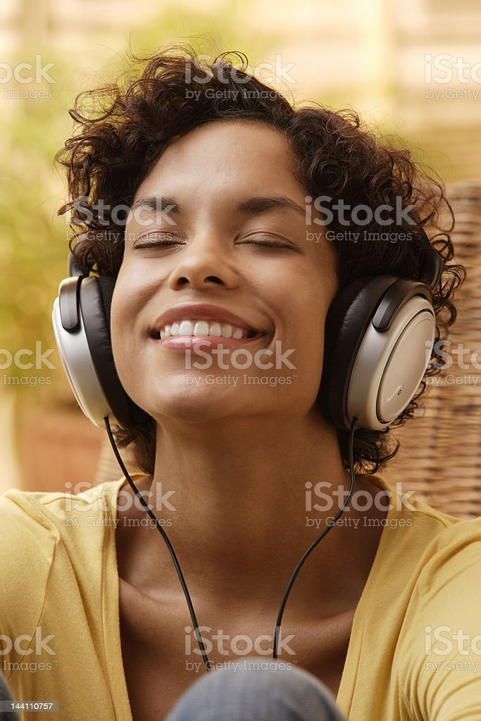 Woman listening to music with big smile and eyes closed.