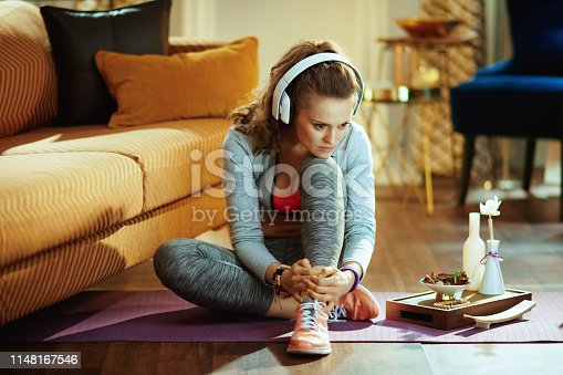 973962328istockphoto woman listening to music with headphones in modern house 1148167546