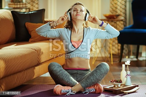 973962328istockphoto woman listening to music with headphones in modern living room 1148155331