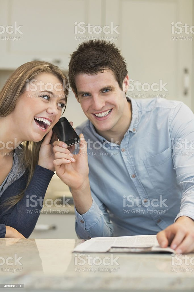 Woman listening to smartphone and laughing stock photo