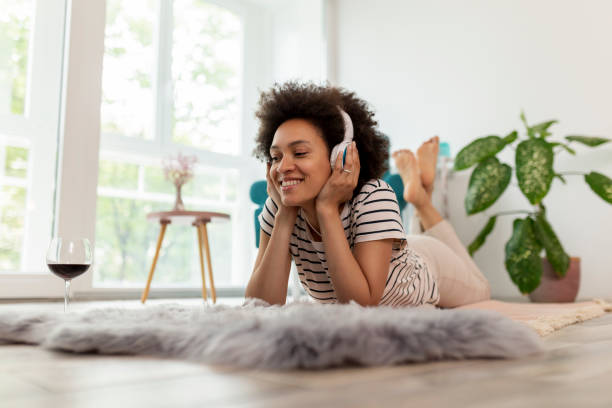 kvinna lyssnar på musik och koppla av hemma - lyssna bildbanksfoton och bilder