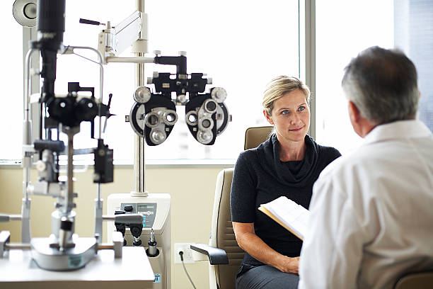 a woman listens to her opthamologist - optometrist stock pictures, royalty-free photos & images