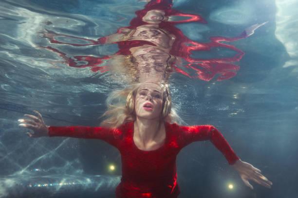 woman listens to music underwater. - frau tiefer ausschnitt stock-fotos und bilder
