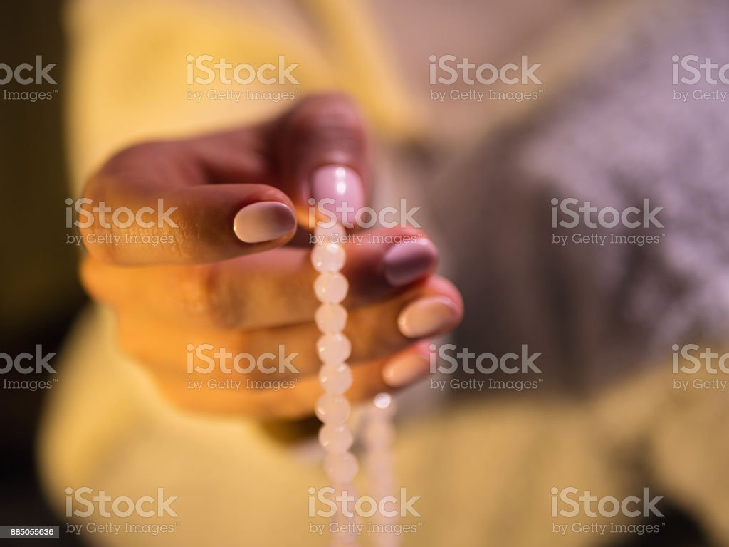 Woman, lit hand close up, counts Malas, strands of gemstones beads used for keeping count during mantra meditations stock photo
