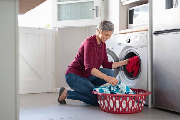 mujer ropa en lavadora de carga - tarea doméstica fotografías e imágenes de stock