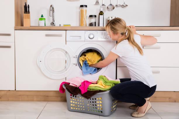 frau laden kleidung in waschmaschine - waschmaschine fotos stock-fotos und bilder