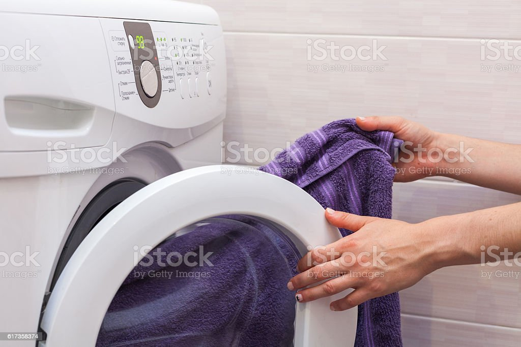 Woman loading laundry to the washing machine stock photo