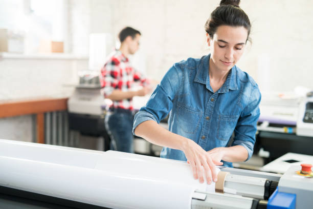 Woman loading wide format printer Serious confident young woman  with hair bun loading wide format printer while working at printing house printing plant stock pictures, royalty-free photos & images