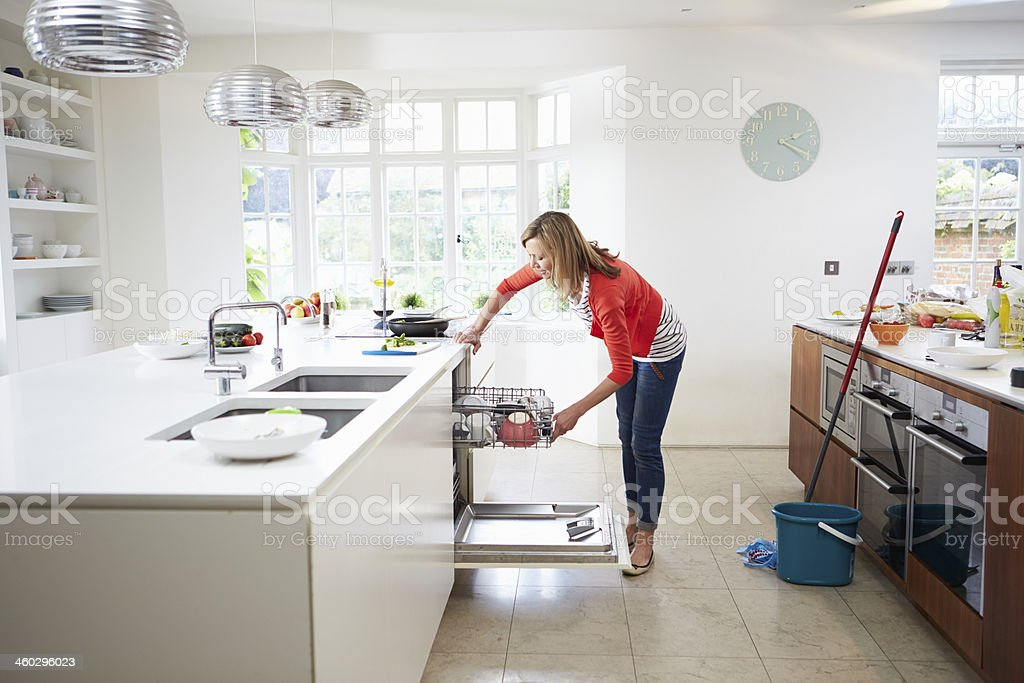 Woman loads plates into dishwasher while cleaning kitchen stock photo