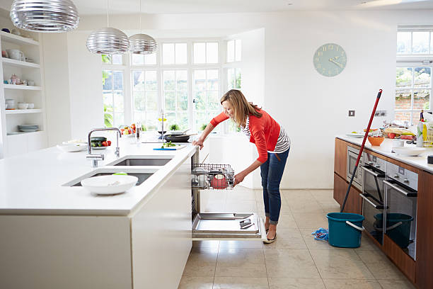 Woman loads plates into dishwasher while cleaning kitchen Woman Bending Down Loading Plates Into Dishwasher dishwasher stock pictures, royalty-free photos & images