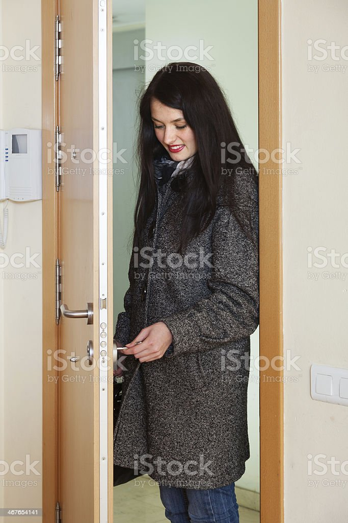 woman loocking door lock stock photo