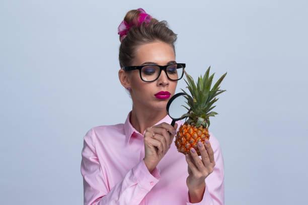 La femme regardent l'ananas par le grossisseur - Photo