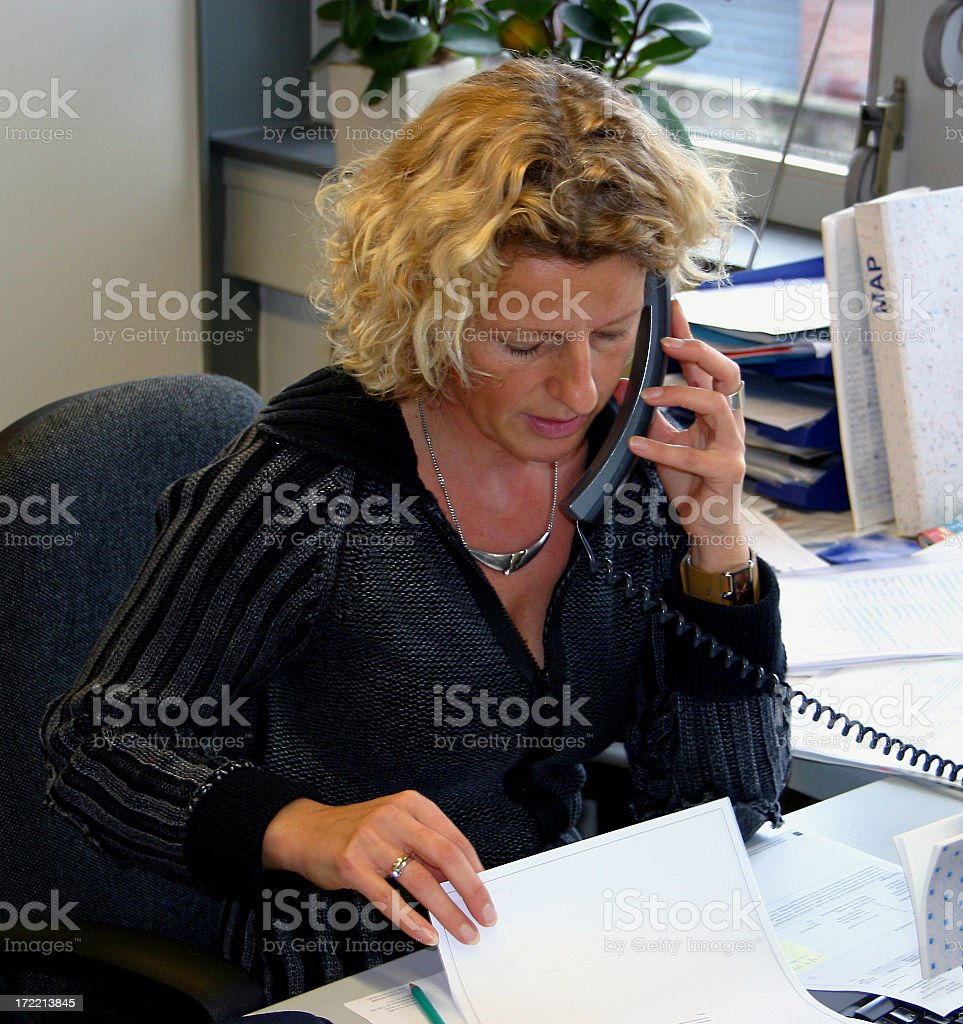 A woman looking at a paper while on the phone in her office royalty-free stock photo